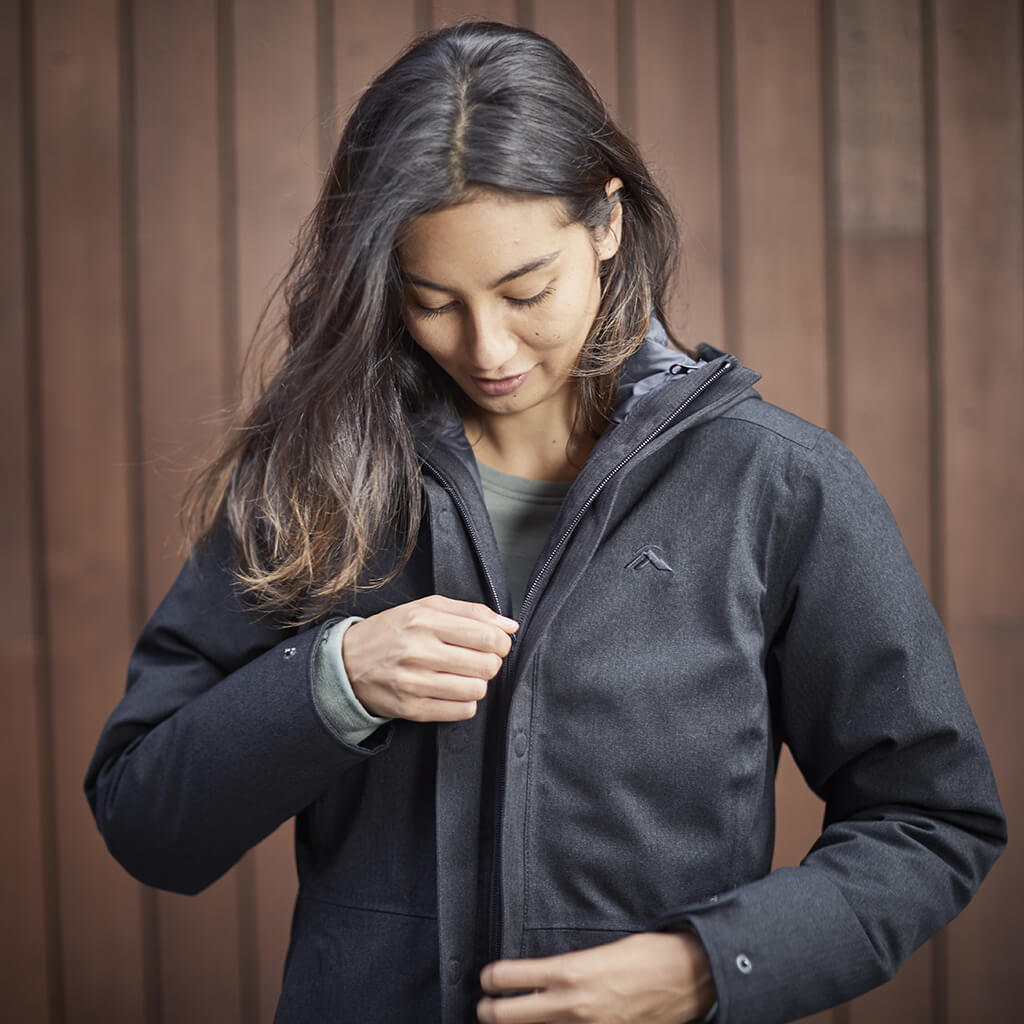 Woman zipping up a black element jacket in front of a timber wall