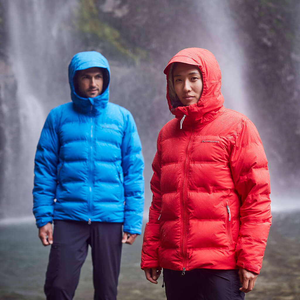 2 people wearing insulated jackets hiking a steep mountain with snow in the background
